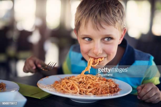 schattige kleine jongen eten spaghetti - spaghetti stockfoto's en -beelden
