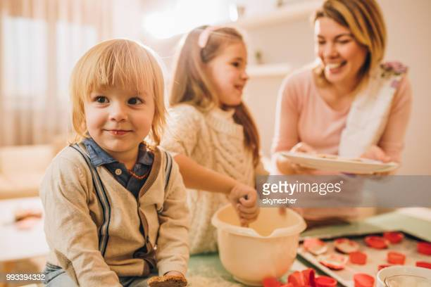 Cute little boy enjoying with his mother and sister in the kitchen.