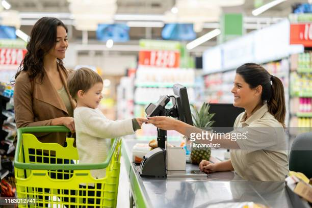 cute little boy handing a loyalty card to cash register before scanning products at checkout in a supermarket - checkout stock pictures, royalty-free photos & images
