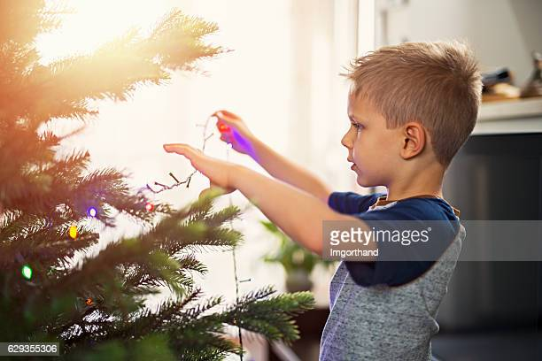 Cute little boy hanging lights on christmas tree