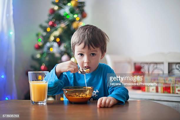 Cute little boy, having breakfast on Christmas day