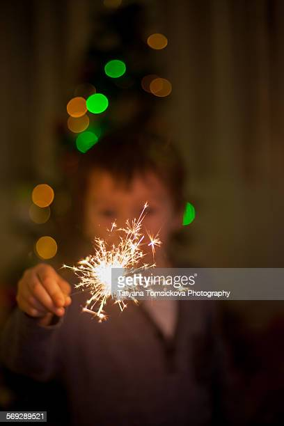 cute little boy, holding sparkler on christmas - bengala fuego artificial fotografías e imágenes de stock
