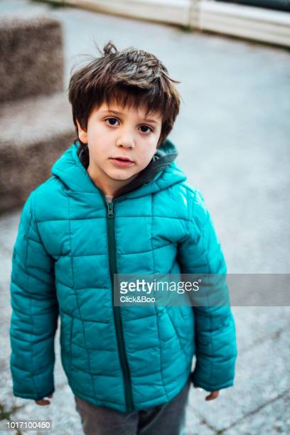 Cute little boy in a blue coat playing outdoors