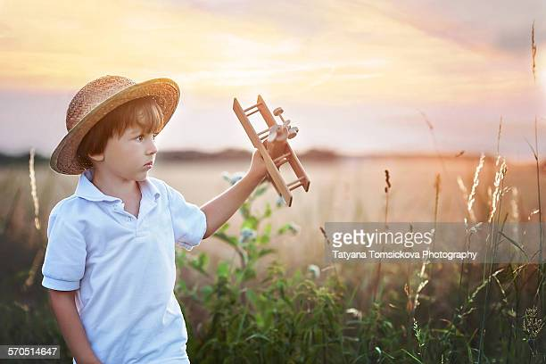 Cute little boy in a field, playing with airplane