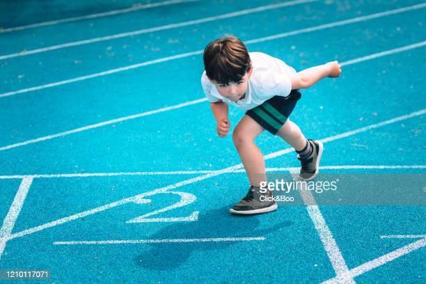 cute little boy in athletics track - click&boo fotografías e imágenes de stock