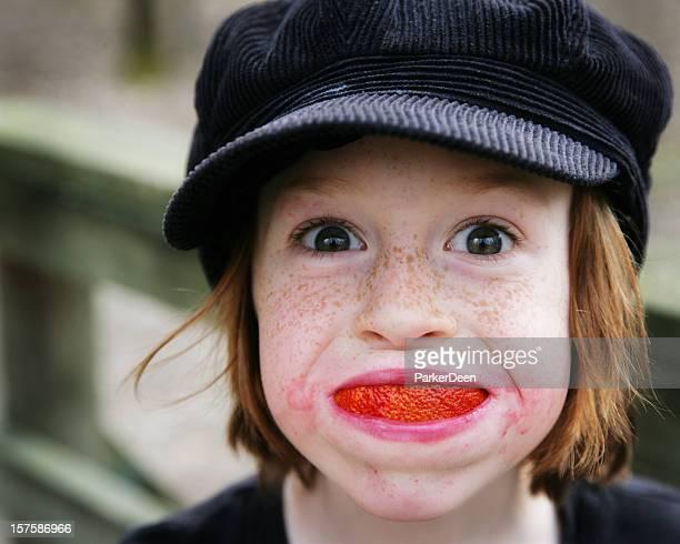 Cute Little Boy in Hat with an Organic Orange Slice