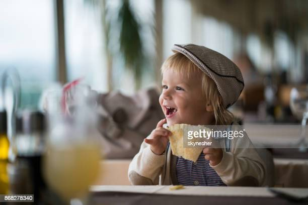 cute little boy is eating bred in restaurant - pizzeria stock photos and pictures