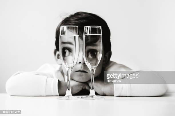 Cute little boy looking through two water glasses