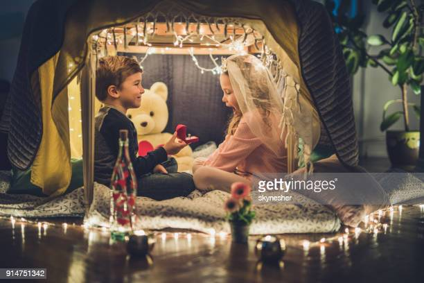 Lindo niño haciendo una sorpresa para su novia mientras le propone en una tienda de campaña.
