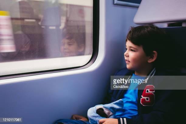 cute little boy on a train, looking through a window - click&boo fotografías e imágenes de stock