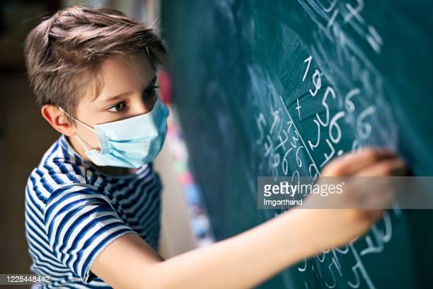 cute little boy on math lesson during covid-19 pandemic - educazione foto e immagini stock