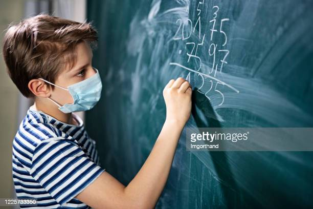 cute little boy on math lesson during covid-19 pandemic - reopening stock pictures, royalty-free photos & images