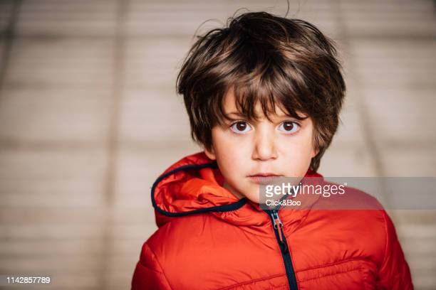 Cute little boy outdoors staring at the camera