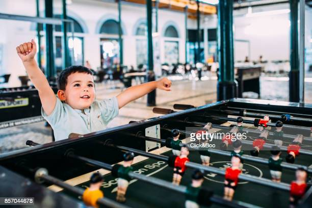 Cute little boy playing a soccer game indoors