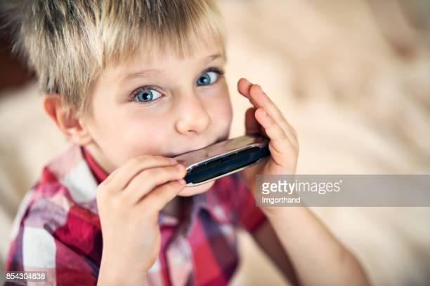 Cute little boy playing harmonica