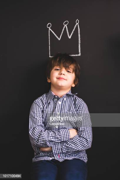 Cute little boy playing indoors. He wears a king's crown drawn on a chalk wall