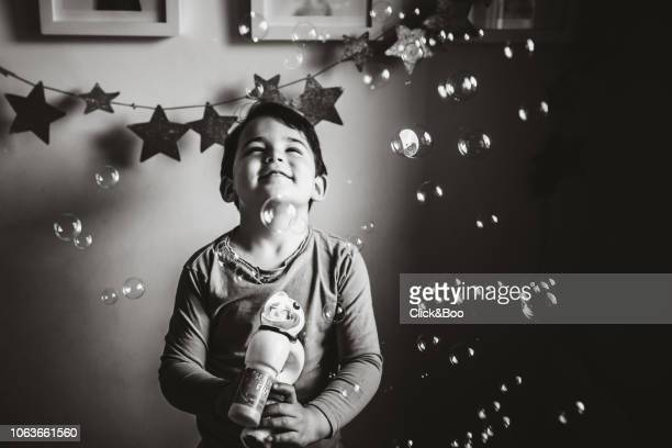 Cute little boy playing indoors with a bubble gun (there is a lot of bubbles)