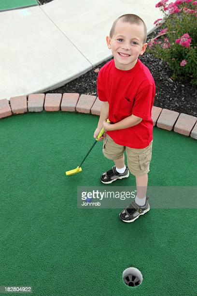 cute little boy playing mini golf ready to putt ball - miniature golf stock photos and pictures
