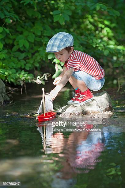 Cute little boy playing on a pond with a toy boat