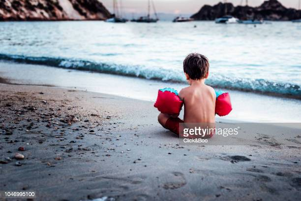 Cute little boy playing on the beach with water wings on the arms