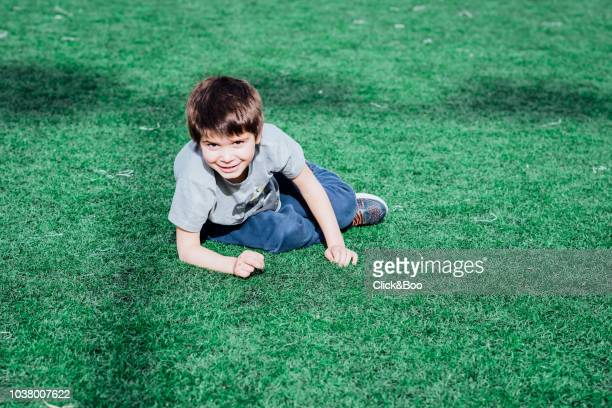 Cute little boy playing outdoors in a sunny afternoon with grass