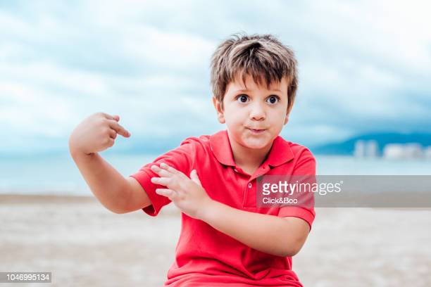 Cute little boy playing outdoors with the beach in the background