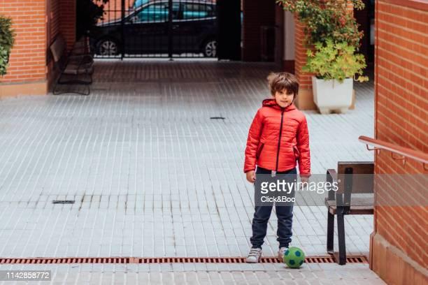 cute little boy playing soccer on the street - click&boo fotografías e imágenes de stock