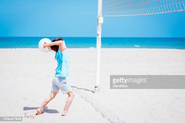 Cute little boy playing volleyball on the beach