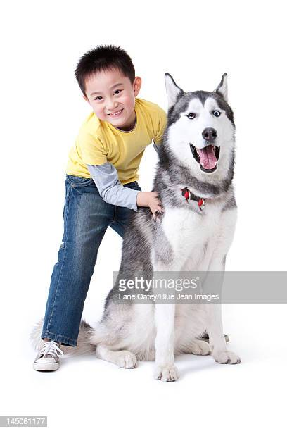 Cute little boy playing with a Husky dog