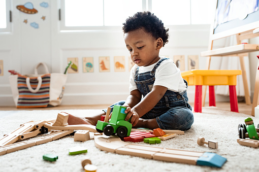 Cute little boy playing with a railroad train toy 1069933778
