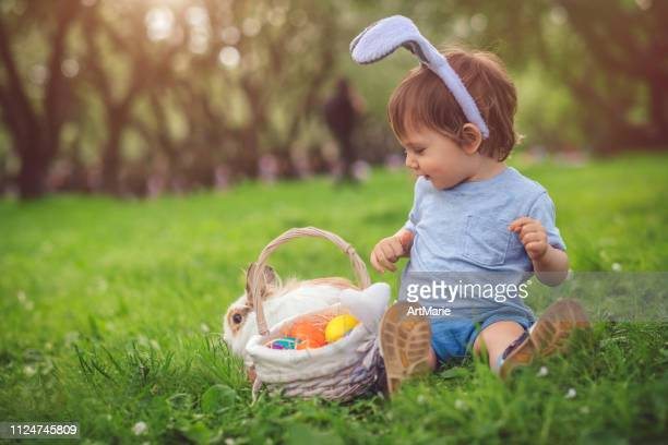 cute little boy playing with bunny and easter eggs - easter bunny stock pictures, royalty-free photos & images