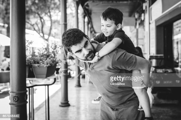 Cute little boy playing with daddy outdoors