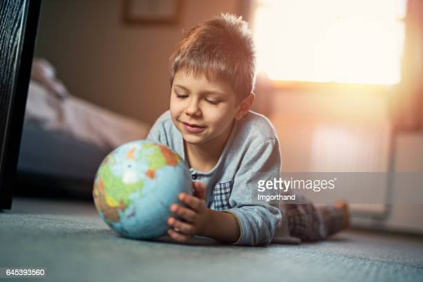 Cute little boy playing with globe on the floor