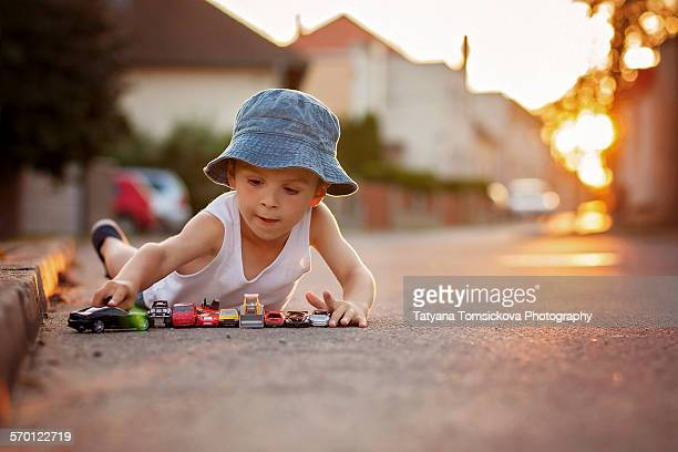 Cute little boy, playing with little toy cars
