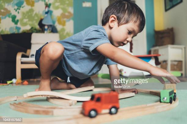 cute little boy playing with wooden train - toy stock pictures, royalty-free photos & images
