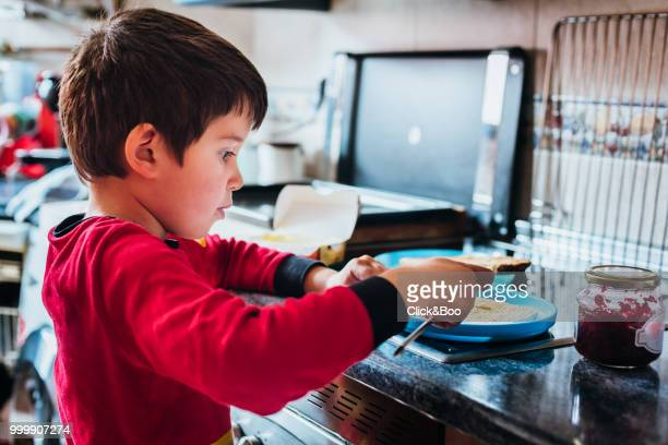 Cute little boy preparing a toasted bread in a kitchen