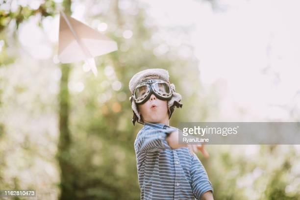 cute little boy pretending to be pilot with paper airplane - aeroplano di carta foto e immagini stock