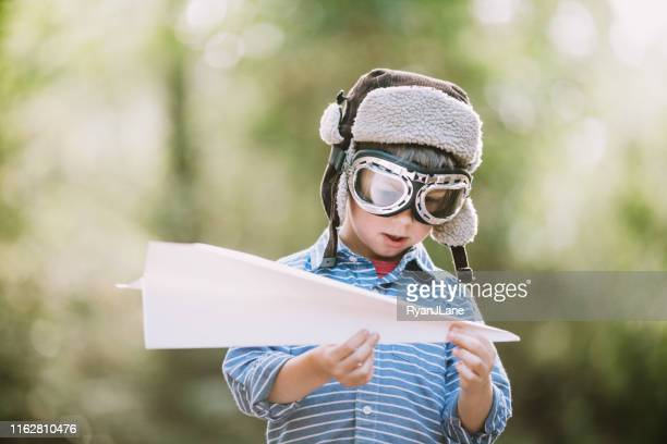 cute little boy pretending to be pilot with paper airplane - aviation hat stock photos and pictures