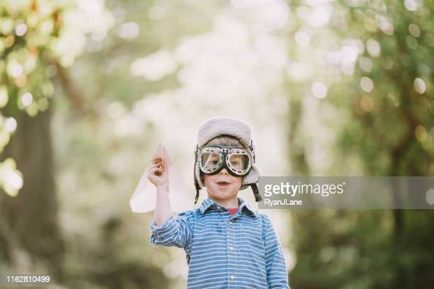 cute little boy pretending to be pilot with paper airplane - aviator's cap stock pictures, royalty-free photos & images
