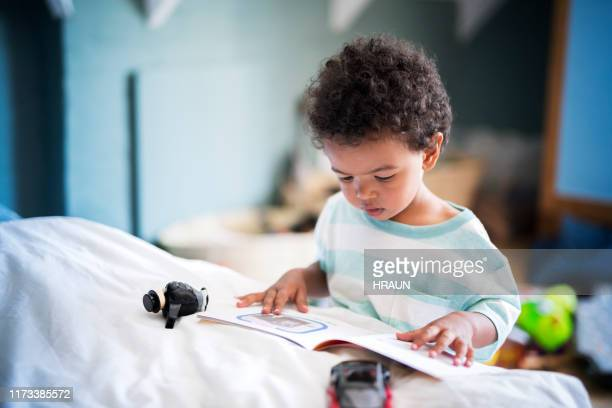 cute little boy reading book at home - picture book stock pictures, royalty-free photos & images
