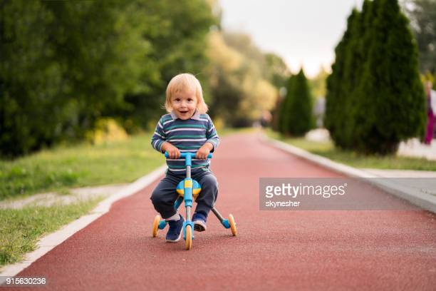 cute little boy riding a tricycle in the park. - tricycle stock pictures, royalty-free photos & images