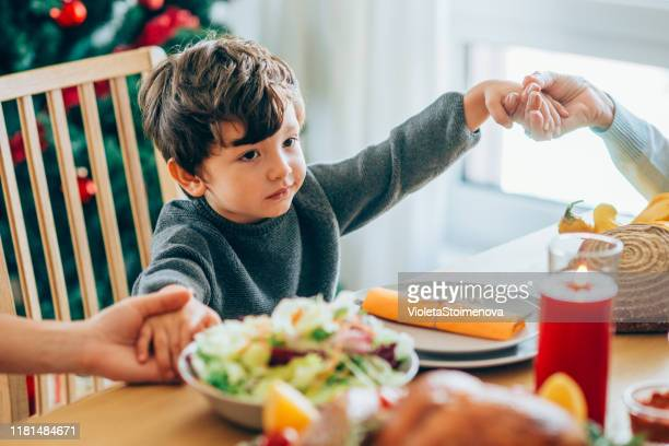 cute little boy says prayer before holiday dinner. - kids thanksgiving stock pictures, royalty-free photos & images
