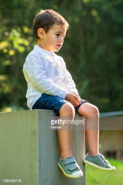 netter kleiner junge sitzt draußen auf einem betonblock - kemter stock-fotos und bilder