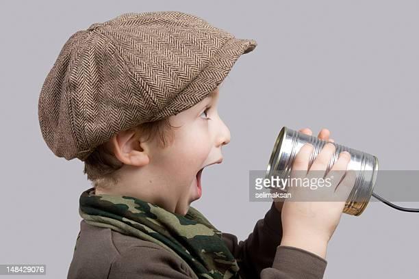 かわいい小さな男の子驚きを伝える糸電話に