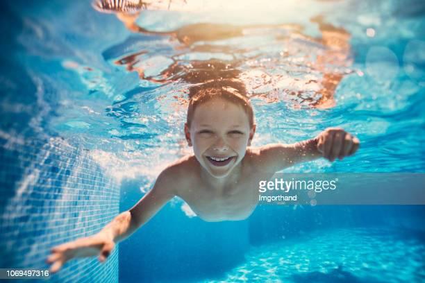 cute little boy swimming underwater in pool - piscina pubblica all'aperto foto e immagini stock