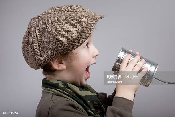 Cute Little Boy Talking And Communicating On Tin Can Phone