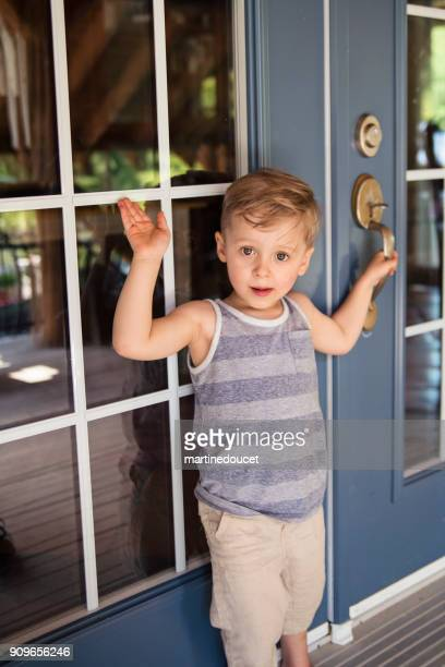 """cute little boy trying to get in the summer house from outdoors. - """"martine doucet"""" or martinedoucet foto e immagini stock"""