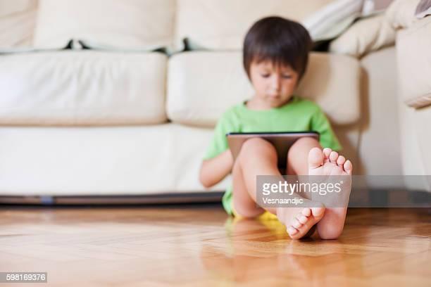 Cute little boy using digital tablet