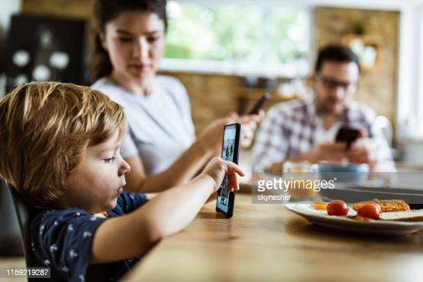 cute little boy watching something on cell phone at dining table. - breakfast cartoon stock pictures, royalty-free photos & images