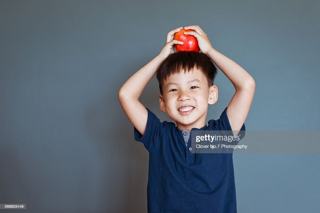 Cute little boy with an apple on his head. : Stock Photo